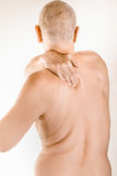 Man suffering of thoracic vertebrae or trapezius muscle pain. Man massaging his top back, the trapezius muscle, because of a thoracic vertebrae pain due to a Royalty Free Stock Photography