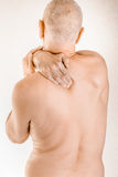 Man suffering of thoracic vertebrae or trapezius muscle pain. Man massaging his top back, the trapezius muscle, because of a thoracic vertebrae pain due to a Royalty Free Stock Photos
