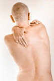 Man suffering of thoracic vertebrae or trapezius muscle pain. Man massaging his top back, the trapezius muscle, because of a thoracic vertebrae pain due to a Royalty Free Stock Images