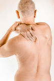 Man suffering of thoracic vertebrae or trapezius muscle pain. Man massaging his top back, the trapezius muscle, because of a thoracic vertebrae pain due to a Stock Image