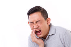 Man suffering from toothache, tooth sensitivity. White isolated background Royalty Free Stock Image