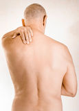 Man suffering of trapezius muscle pain. Man massaging his shoulder, because of a trapezius muscle pain due to a displacement of a dorsal vertebra rubbing on a Royalty Free Stock Photos