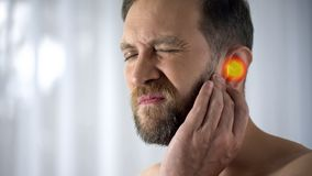 Man suffers from earache, otitis, hearing problems, spot indicates pain, closeup. Stock photo stock photo