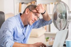 Man suffers from heat in the office or at home. Man suffers from heat while working in the office and tries to cool off by the fan stock images