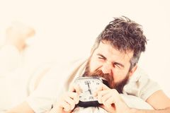 Man suffers in morning, wants to destroy alarm clock. White background. Guy with furious face bites alarm clock. Hipster with beard and mustache awake because stock photos