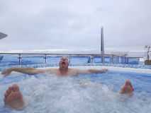 Man suffocating in hot tub. Man grimmacing in hot tub on cruise ship in ice field of Antarctica Royalty Free Stock Photo