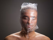 Man suffocating with plastic around his head. On dark background Royalty Free Stock Photography