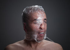 Man suffocating with plastic around his head. Isolated on dark background Stock Images