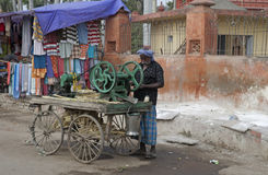 Man with sugar cane pressing machine mounted on a cart. Royalty Free Stock Image