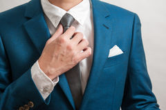Man in suit adjusting necktie Stock Images