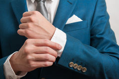Man in suit adjusting sleeves Royalty Free Stock Photo