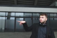 A man in a suit against the background of modern architecture shows his hand in the other direction. Stock Images