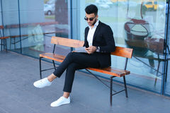 Man in suit arabic puts on sunglasses with tablet near business Royalty Free Stock Image