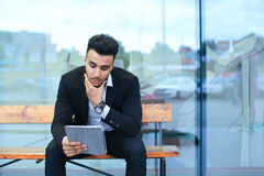 Man in suit arabic puts on sunglasses with tablet near business Stock Image