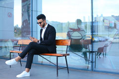Man in suit arabic puts on sunglasses with tablet near business Stock Photo