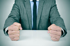 Man in suit banging his fists on a desk. Closeup of a young caucasian man wearing a gray suit banging his fists on his office desk Royalty Free Stock Image