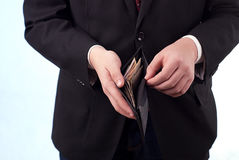 A man with banknotes in wallet. Man in suit with banknotes in wallet Royalty Free Stock Images