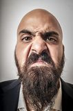 Man with a suit and beard and strange expressions Stock Photos