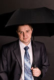 The man in suit with black umbrella Stock Photo