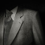 Man suit in black. Black & White film photo of man suit detail against black background. Low key exposure to give it a sinister semblance Royalty Free Stock Photography