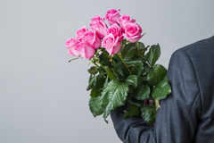 Man in suit with bouquet of pink roses Stock Image
