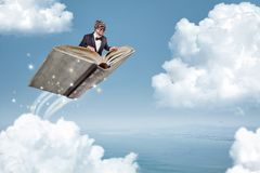 Man flying on a book over the clouds. A man in a suit and bow tie is flying over the clouds whilst sitting on a book Royalty Free Stock Photo