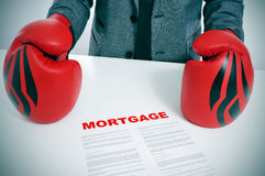 Man in suit with boxing gloves and a mortgage contract. Man wearing a suit and boxing gloves with a mortgage contract on his desk Stock Photography