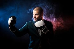 Man in suit boxing. Handsome man sportsman in white shirt, green jacket, black and white boxing gloves boxing and ready to tackle any opposite of red and blue Stock Images
