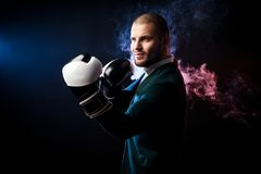 Man in suit boxing. Young handsome businessman man in white shirt, green jacket, black and white boxing gloves smiling and ready to box against the red and blue Stock Photography