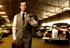 Man in suit with briefcase. Businessman with a briefcase in garage stock photo
