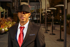 Man in suit in business park. A young man in a suit with a red tie and hat standing in front of alley Stock Photography