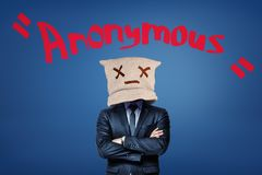 A man in suit with a canvas bag on his head with a dead emoticon on it, standing with arms folded, with the title. `Anonymous` above. Guarantee of anonymity stock image
