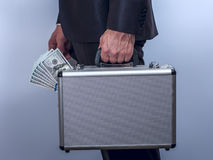 Man in suit carries metal briefcase with dollars. On grey background.  Conception of safe storage and protection of cash. Financial theme. Horizontal view Stock Images