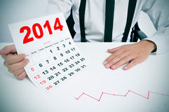 Man in suit with a chart and a 2014 calendar. Businessman sitting in a desk with a chart and showing a 2014 calendar Royalty Free Stock Photography