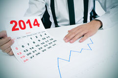 Man in suit with a chart and a 2014 calendar. Businessman sitting in a desk with a chart and showing a 2014 calendar Royalty Free Stock Images