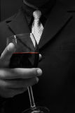Man in suit. Classy and sophisticated man in tuxedo suit drinking wine Stock Photos