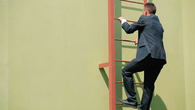 The man in suit climb up the stairs stock footage