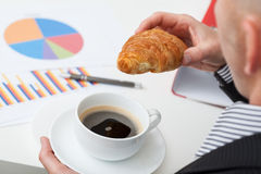 Man in suit with coffee and roll. Man in suit with cup of coffee and roll above the charts royalty free stock photos