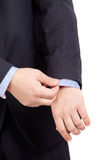 Man in suit correcting a sleeve Stock Images