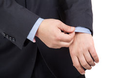 Man in suit correcting a sleeve Royalty Free Stock Image
