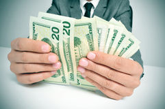 Man in suit counting US dollar bills. A man wearing a suit sitting in a desk counting US dollar bills Stock Photos