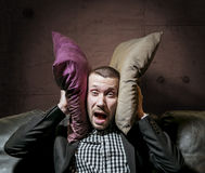 A man in a suit covering her ears with pillows and screaming fro. A man in a business suit covering her ears with pillows and screaming from the nerves royalty free stock photo