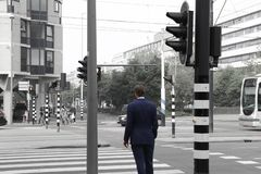 Man in suit crossing the road stock image