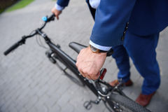 Man in suit cycling on road Stock Photo