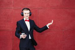 Man in a suit is dancing. Young guy is listening to music in big headphones through smartphone. Concept of good mood and. Relaxation stock photo