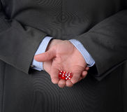 Man in suit with dice behind his back Royalty Free Stock Photography