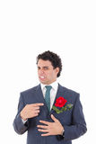 Man in suit with disgust shows with his hand flower which is in Stock Photos