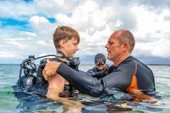A man in a suit for diving prepares a boy to dive. A men in a suit for diving prepares a boy to dive royalty free stock photos