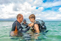 A man in a suit for diving prepares a boy to dive. A men in a suit for diving prepares a boy to dive stock photos
