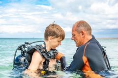 A man in a suit for diving prepares a boy to dive stock image